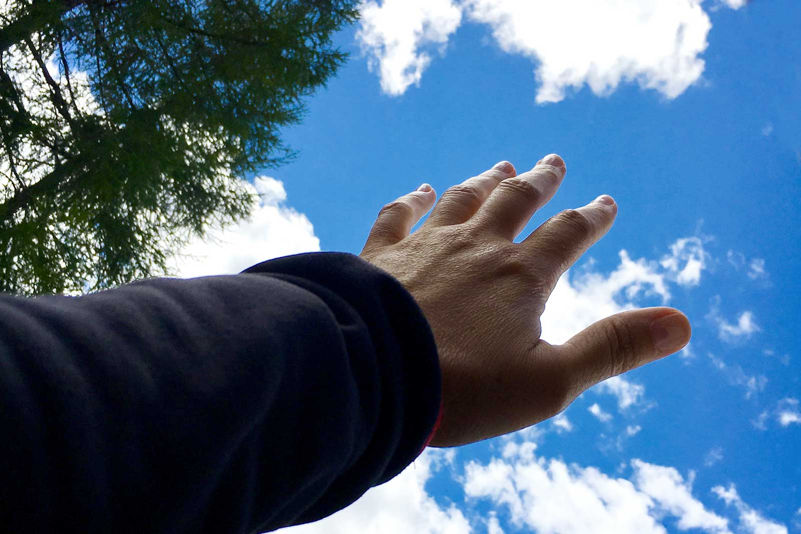 mano verso cielo blu